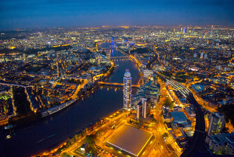 Aerial photo of London at night, featuring The Tower, One St George Wharf and Nine Elms regeneration area in the foreground.