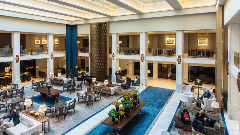 Hotel lobby at Tivoli Avenida Liberdade, refurbished with the historic glamour of gold screens and blue velvets.
