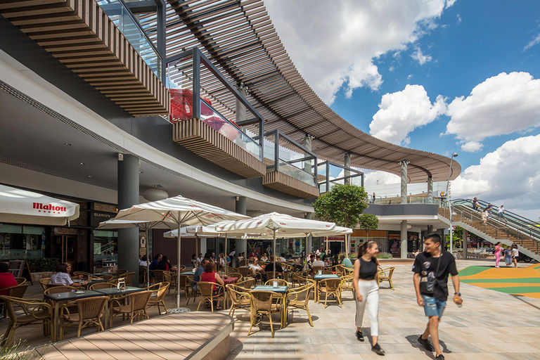 Exterior restaurant terraces and new waved canopy at Quadernillios retail centre in Alcalà de Henares, Spain.