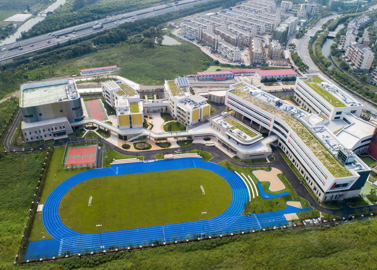 Aerial site view of academic buildings and outdoor sports track at Jiading School, a new private school in Shanghai, China.